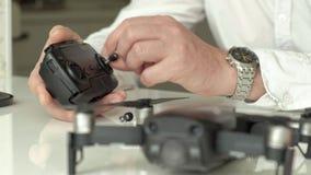 De rijpe mens met glazen en een wit overhemd assembleert een controlebord voor een quadrocopter, een concept voor de studie van stock videobeelden
