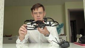 De rijpe mens met glazen en een wit overhemd verzamelt een quadrocopter, onderzoekt het, het concept het bestuderen van technolog stock videobeelden