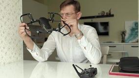De rijpe mens met glazen en een wit overhemd verzamelt een quadrocopter, onderzoekt het, het concept het bestuderen van technolog stock video
