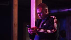 De rijpe mens in sport Jersey houdt smartphone binnen donkere zaal indient stock footage