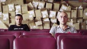 De rijpe mensen zitten in rij van purpere stoelen met grote stapel van dozen achter hun ruggen stock video