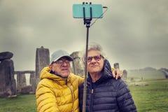 De rijpe mensenvrienden nemen een selfie in Stonehenge-archaeologica Stock Foto's