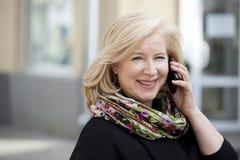 De rijpe mooie blondevrouw nodigt een celtelefoon uit Royalty-vrije Stock Foto
