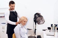 De rijpe mooie vrouw doet kapsel in schoonheidssalon Vrouwelijk modieus kapsel stock fotografie