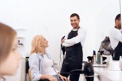 De rijpe mooie vrouw doet kapsel in schoonheidssalon Vrouwelijk modieus kapsel stock afbeeldingen
