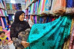 De rijpe Moslimvrouw in hijab kiest stof op de markt stock foto