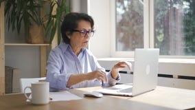 De rijpe onderneemster werkt met laptop zitting in de ruimte van het huisbureau stock video