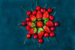 De rijpe organische aardbeien, glanzende zoete kersen schikten in vorm van bloem, blauwe achtergrond, gestileerd creatief beeld Royalty-vrije Stock Foto's