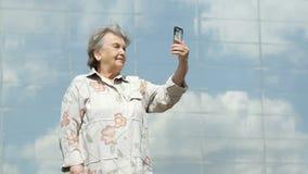 De rijpe oude vrouw neemt foto's gebruikend een slimme telefoon stock video
