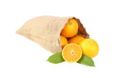 De rijpe sinaasappelen liggen in een strozak Stock Afbeeldingen