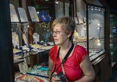 De rijpe toeristenvrouw bekijkt showcase van gouden juwelenwinkel Stock Afbeelding