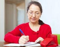 De rijpe vrouw is berekende familiebegroting Stock Afbeelding