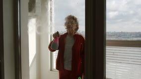 De rijpe vrouw bespuit vensterreinigingsmachine binnen op groot venster - zijaanzicht stock videobeelden