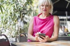De rijpe vrouw die van het blondehaar een mobiele telefoon in openlucht met behulp van royalty-vrije stock foto
