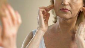De rijpe vrouw die zwaar het bekijken haar zuchten rimpelde en huid in spiegel verzakken stock videobeelden