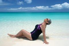 De rijpe vrouw doet leunen op oorspronkelijk strand Stock Afbeelding