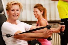 De rijpe vrouw in de gymnastiek leidt haar wapens met een gewichtsheftoestel op stock afbeeldingen