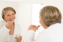 De rijpe vrouw het borstelen tanden kijken badkamersspiegel royalty-vrije stock fotografie