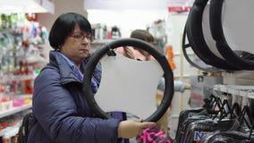 De rijpe vrouw kiest binnen een zachte versiering voor het stuurwiel van een auto