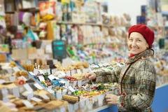 De rijpe vrouw kiest snoepjes Royalty-vrije Stock Foto