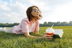 De rijpe vrouw ligt op groen gras Het wijfje in het park met de zomerdrank, boek, rust en meditatie, kopieert ruimte, gouden uur stock fotografie