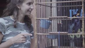 De rijpe vrouw met verbaasd gezicht richt met vinger op grote houten kooi met vogel stock video