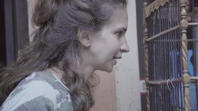 De rijpe vrouw met verbaasd gezicht staart bij grote houten kooi met zwarte binnen vogel stock footage