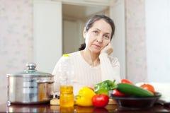 De rijpe vrouw van de uitputting bij keuken stock foto