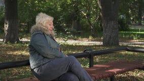 De rijpe vrouw wacht in het park stock videobeelden