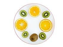 De rijpe vruchten van sinaasappel en kiwi worden gesneden in ronde plakken op een witte porseleinplaat met een granaatappelrand Stock Foto