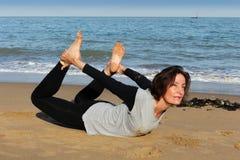 De rijpe yoga van de vrouwenboog op het strand Stock Afbeeldingen