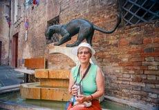 De rijpe zitting van de toeristenvrouw bij fontein met monument van panter Stock Fotografie