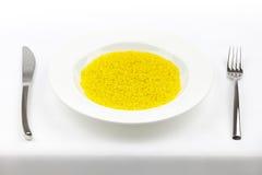 De rijst van de saffraan met vork en mes op tafelkleed Stock Foto
