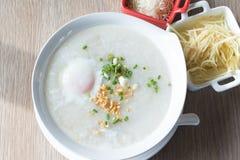 De rijsthavermoutpap kookte rijst met ei, gember en ui op houten lijst, Thais voedsel Stock Afbeeldingen