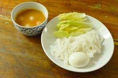 De rijstnoedels en het gekookte ei eten paar met vissenkerrie op kom stock fotografie