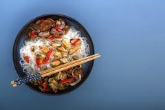 De rijstnoedels met zeevruchten, salade, Spaanse peper en gebraden paddestoelen in een traditioneel porselein plateren op een bla royalty-vrije stock afbeelding