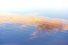 De rimpelingen van het water. Blauwe, oranje, gele tinten Stock Foto's