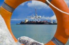 De ring van de het levensveiligheid en vrachtschip bij zeehaven Stock Afbeeldingen