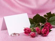 De ringen, de kaart en de rozen van de zilveren bruiloft Stock Fotografie