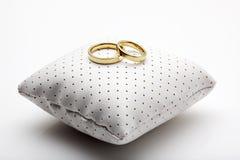 De ringen van de gouden bruiloft op klein kussen Stock Afbeeldingen