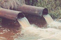 de rioolpijpen gieten aan de rivier/rioolpijpen uit uitgieten aan de rivier gestemd stock foto