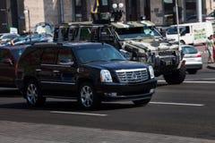 De ritten van Cadillac Escalade rond stad stock fotografie