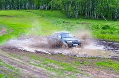 De ritten van de jeepauto in de modder met plonsen Rusland, Tyumen Juni 2014 Stock Foto