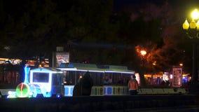 De ritten van de kinderen` s trein op de kade bij nacht stock videobeelden