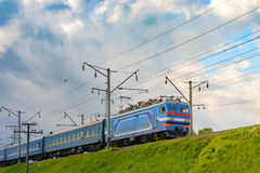 De ritten van de passagierstrein op een geëlektriseerde lijn tegen een blauwe hemel stock foto's
