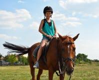 De ritten van het meisje op een paard Stock Foto's