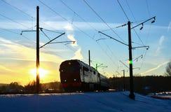 De ritten van de passagierstrein door trein bij zonsondergang stock fotografie