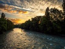De rivier Arve, Zwitserland, in diepe schaduw als hemel wordt verlicht door de het toenemen zon royalty-vrije stock afbeelding