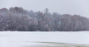 De rivier is behandeld met ijs en een sneeuwdeken Donkere bomen aan de andere kant van de rivier in de mist Stock Afbeeldingen