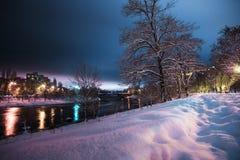 De rivier en de huizen met meerdere verdiepingen bij sneeuwnacht Royalty-vrije Stock Fotografie